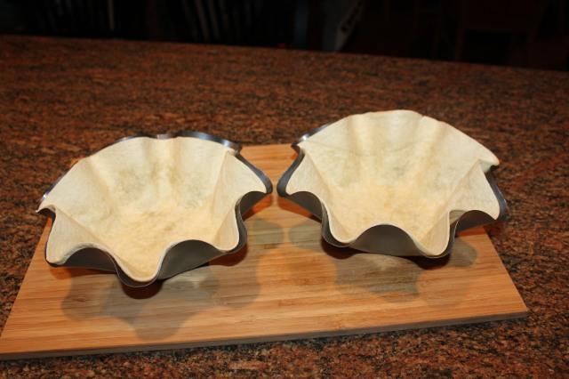 Press tortilla shells into pans